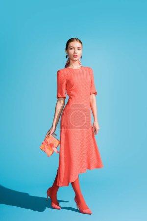 Photo pour Boîte sur bleu-cadeau femme élégante en tenue robe corail vivant - image libre de droit