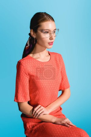 Photo for Fashionable girl posing in trendy living coral dress isolated on blue - Royalty Free Image