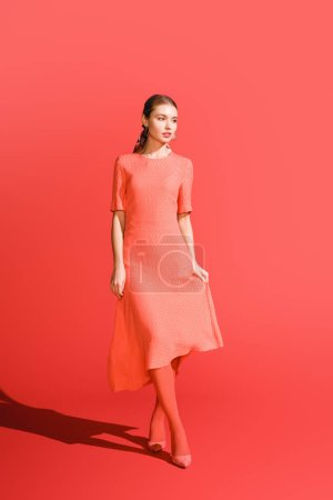 stylish girl posing in living coral dress on red background