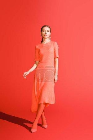 attrayant élégant fille posant dans la robe de corail vivant sur fond rouge