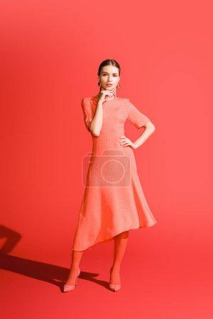 Photo pour Élégant jeune femme posant dans la robe de corail vivant sur fond rouge - image libre de droit