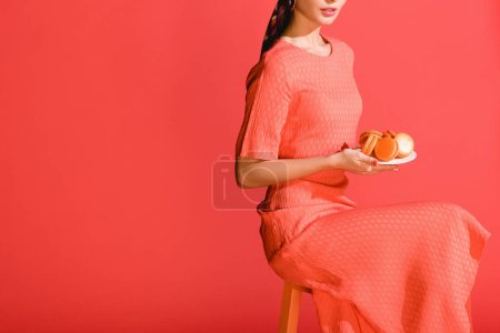 Photo for Cropped view of stylish girl holding plate with macaroons isolated on living coral. Pantone color of the year 2019 concept - Royalty Free Image
