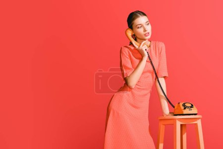 Photo for Fashionable woman with vintage rotary phone isolated on living coral. Pantone color of the year 2019 concept - Royalty Free Image