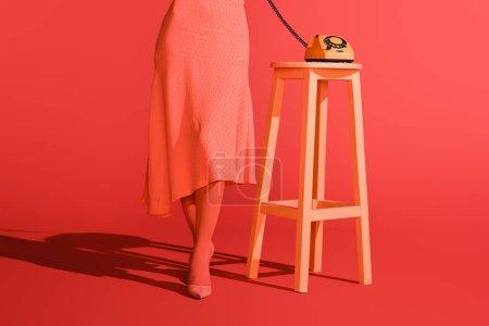 Photo pour Vue en coupe bas de femme avec rétro téléphone rotatif sur tabouret sur corail vivant. Couleur Pantone de la notion d'année 2019 - image libre de droit