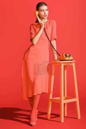 Photo for Beautiful woman posing with retro rotary telephone on living coral. Pantone color of the year 2019 concept - Royalty Free Image