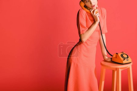 Photo for Attractive stylish model with vintage rotary phone isolated on living coral. Pantone color of the year 2019 concept - Royalty Free Image
