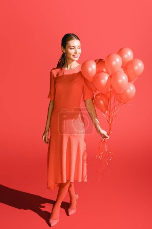 Photo for Smiling fashionable girl posing with living coral balloons. Pantone color of the year 2019 concept - Royalty Free Image