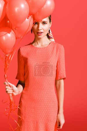 Photo for Attractive girl posing with living coral balloons. Pantone color of the year 2019 concept - Royalty Free Image