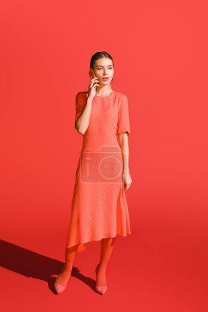 Foto de Moda mujer en vida coral vestido hablando por el teléfono inteligente en rojo. Color pantone del concepto año 2019 - Imagen libre de derechos