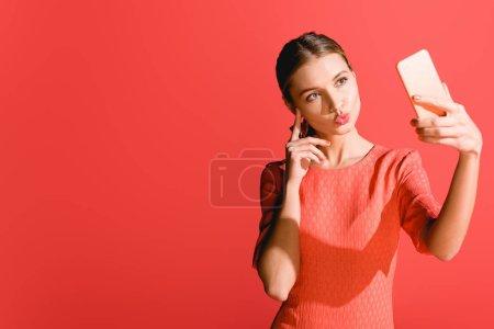 Foto de Mujer atractiva en vida vestido coral toma selfie en smartphone en rojo. Color pantone del concepto año 2019 - Imagen libre de derechos