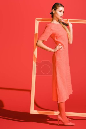Photo for Fashionable model in dress posing with big frame on living coral. Pantone color of the year 2019 concept - Royalty Free Image