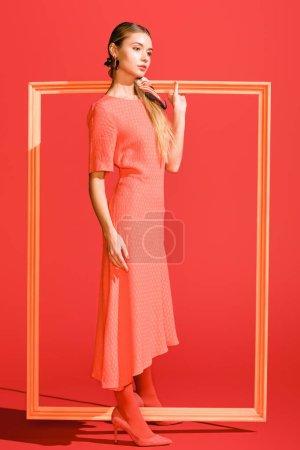Foto de Moda joven en vestido de moda con marco grande en coral vivo. Color pantone del concepto año 2019 - Imagen libre de derechos