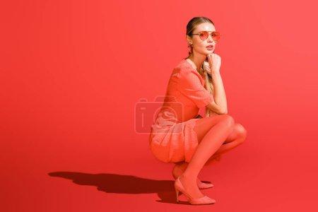 Photo pour Élégant modèle posant en corail vivant vêtements et lunettes de soleil sur fond rouge - image libre de droit