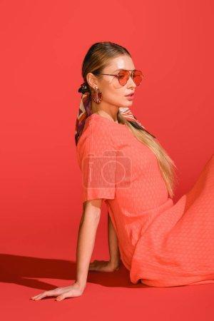 Photo pour La mode élégant modèle posant la vie robe corail et lunettes de soleil sur fond rouge - image libre de droit