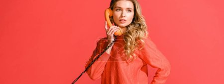 Photo for Attractive woman with retro rotary phone isolated on living coral. Pantone color of the year 2019 concept - Royalty Free Image