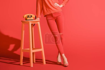Photo for Cropped view of stylish woman posing with retro rotary telephone on living coral. Pantone color of the year 2019 concept - Royalty Free Image