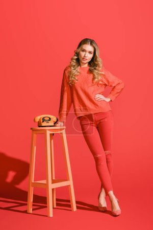 Photo for Fashionable girl posing with vintage rotary telephone on living coral. Pantone color of the year 2019 concept - Royalty Free Image