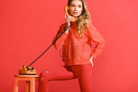 Foto de Mujer atractiva posando con retro teléfono rotatorio aislado en la vida coral. Color pantone del concepto año 2019 - Imagen libre de derechos