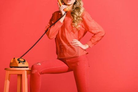 Photo for Cropped view of girl posing with retro rotary telephone isolated on living coral. Pantone color of the year 2019 concept - Royalty Free Image
