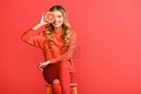 Foto de Niña de moda sonriente posando y pomelo aislado en la vida coral. Color pantone del concepto año 2019 - Imagen libre de derechos