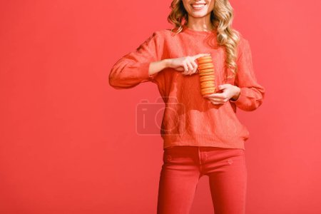 Photo for Cropped view of smiling woman holding macaroons isolated on living coral. Pantone color of the year 2019 concept - Royalty Free Image
