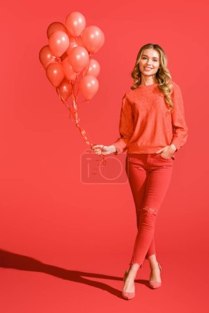 Photo for Cheerful fashionable girl posing with living coral balloons. Pantone color of the year 2019 concept - Royalty Free Image
