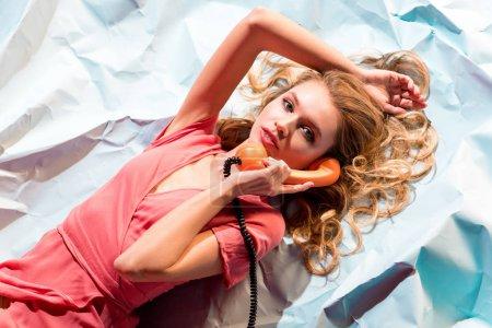 Foto de Vista superior de la mujer rubia hablando por teléfono vintage mientras se está acostado en la luz azul arrugado de papel - Imagen libre de derechos