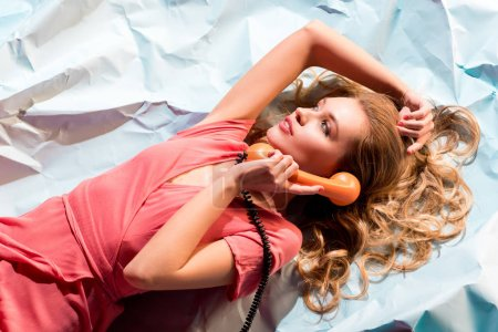 Photo for Top view of elegant blonde girl talking on vintage rotary phone while lying on light blue crumpled paper - Royalty Free Image