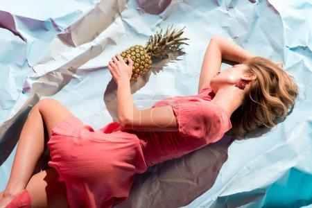 Photo pour Vue du dessus de la fille élégante en robe de corail vivant tenant l'ananas et couché sur du papier froissé bleu clair - image libre de droit