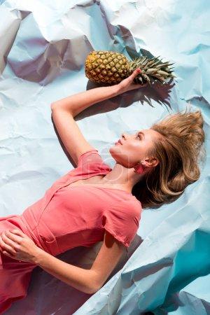 Photo pour Vue du dessus de la jolie femme blonde en robe de corail vivant tenant l'ananas frais et couché sur du papier froissé bleu clair - image libre de droit
