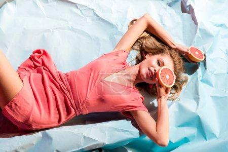 Photo pour Vue du dessus de l'élégante fille souriante en robe de corail vivant tenant des moitiés de pamplemousse frais et couché sur du papier froissé bleu clair - image libre de droit