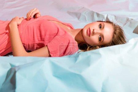 Photo pour Attrayant jeune femme dans élégante robe de corail vivant couché sur papier froissé bleu clair - image libre de droit