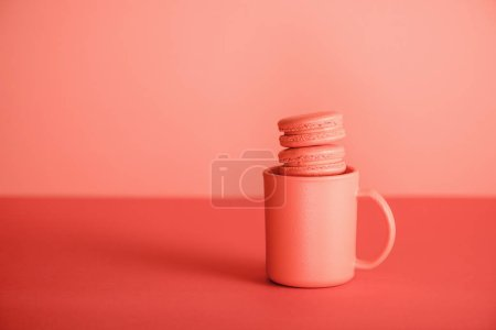 Photo for Sweet macaroons in cup on Living coral background. Pantone color of the year 2019 concept - Royalty Free Image