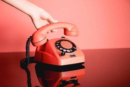 Foto de Vista parcial de la mujer con vida coral teléfono rotatorio vintage. Color pantone del concepto año 2019 - Imagen libre de derechos