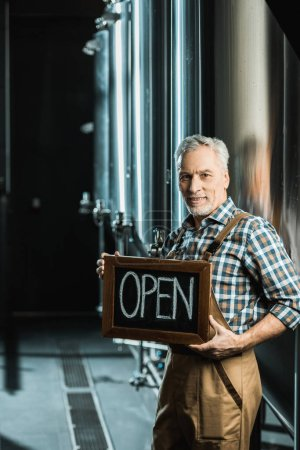Photo for Successful senior owner holding board with open sign in brewery - Royalty Free Image