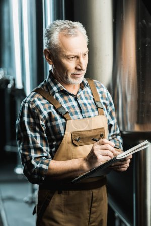 Photo for Professional male brewer in working overalls writing in notepad in brewery - Royalty Free Image