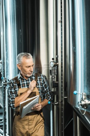 Photo for Handsome senior brewer in working overalls holding notepad and looking at brewery equipment - Royalty Free Image