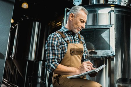 Photo for Professional brewer in working overalls writing in notepad while examining brewery equipment - Royalty Free Image