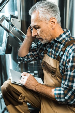 Photo for Senior male brewer in working overalls talking on smartphone while writing in notepad in brewery - Royalty Free Image