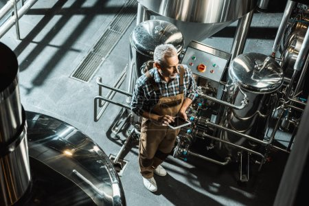 Photo for Overhead view of brewer in working overalls using digital tablet in brewery - Royalty Free Image