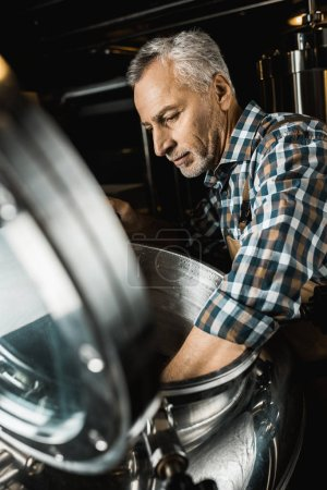 Photo pour Professionnel brewer mâle en salopettes de travail inspecter l'équipement de la brasserie - image libre de droit