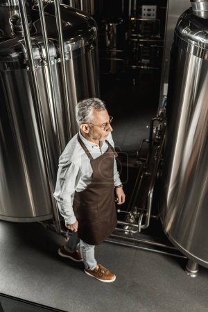 Photo pour Masculin senior brasseur au tablier marchant dans la brasserie - image libre de droit