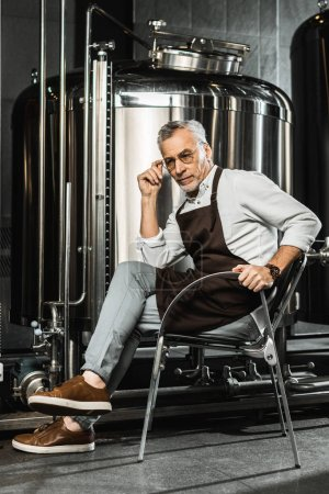 senior brewer in apron sitting on chair in brewery
