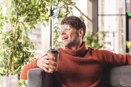 Photo pour Homme gai dans des lunettes tenant tasse en papier dans le café - image libre de droit