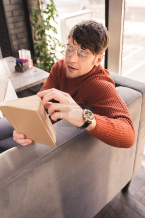 Photo pour Bel homme dans les lunettes livre de lecture dans le café - image libre de droit