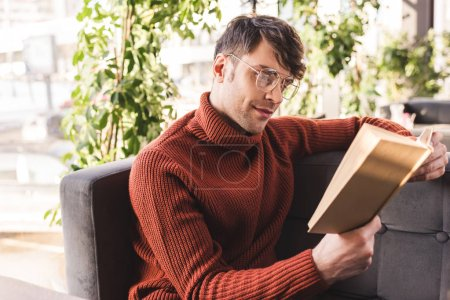 handsome man in glasses reading book while sitting in cafe