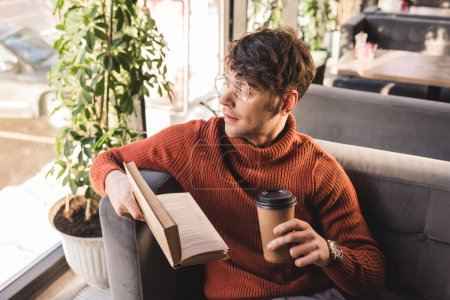 Photo for Pensive young man in glasses holding book and paper cup in hands - Royalty Free Image