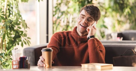 selective focus of cheerful man in glasses talking on smartphone near paper cup with coffee and book