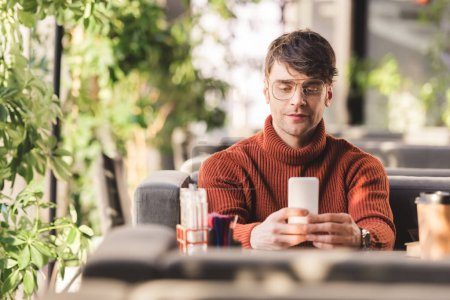 Photo for Cheerful man using smartphone near disposable cup in cafe - Royalty Free Image