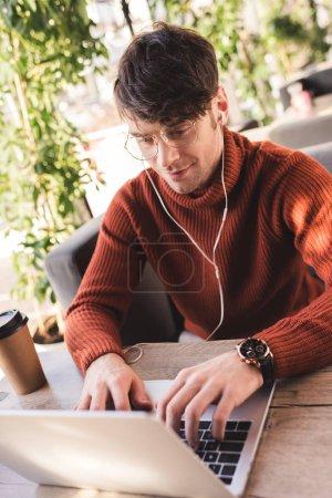 Photo pour Homme gai écouter de la musique dans les écouteurs tout en utilisant un ordinateur portable dans le café - image libre de droit